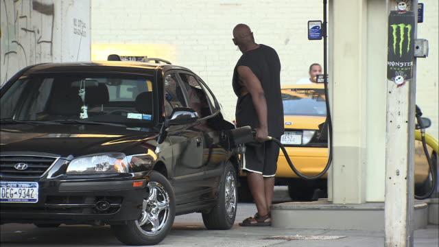 WS, Man filling car at Manhattan gas station, rear view, New York City, New York, USA