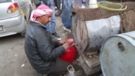 A man fills a container with gasoline and fixes a tire in Aleppo Syria
