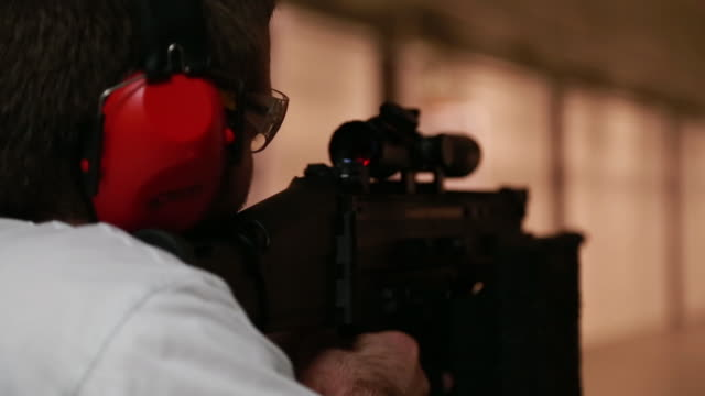 A man fires an assault rifle with a silencer attachment