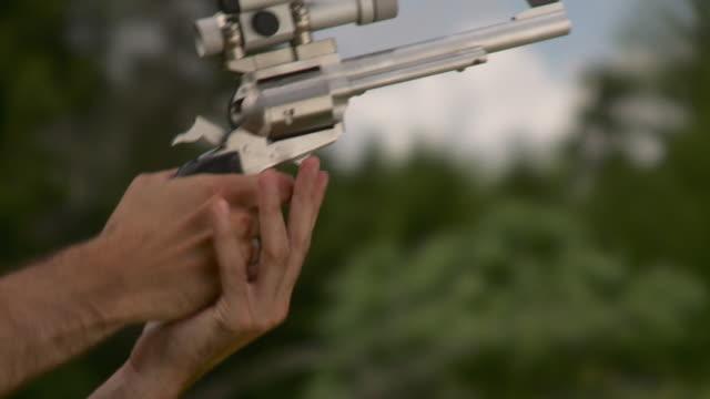 CU Man firing revolver with laser scope, Stowe, Vermont, USA