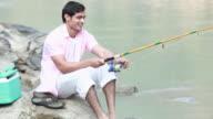Man fishing at riverbank