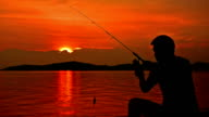Man fishing on pier at sunrise.