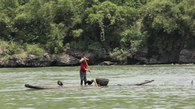 WS Man fishing riding traditional boat and ferry passing from back / Close to Li River, Guangxi, China