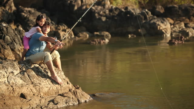 Man fishing with his daughter at lakeside