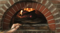 man flipping pizza dough in a wood fired oven