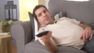 Man flipping through channels on couch