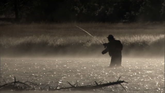 Man fly fishing in steaming river, Yellowstone, USA