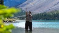 Mann Fliegenfischen auf dem Berg lake