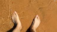 Mens voet staande op het strand