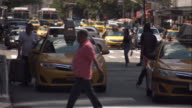 Man gets into taxi cab with his luggage on busy New York City street