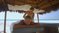 MS Man getting massage in hut on beach/ Tulum, Mexico