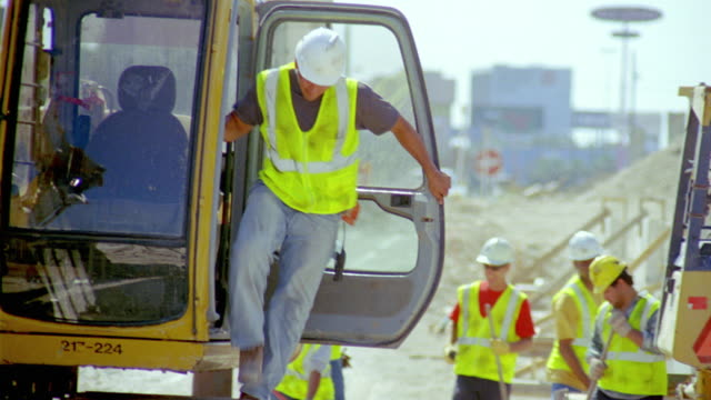 MS, man getting off bulldozer, workers shifting rubble in background, San Antonio, Texas, USA
