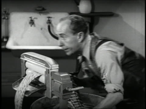B/W 1941 man getting tie stuck in wringer of early washing machine / woman cutting tie with scissors