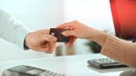 Uomo dando la sua carta di credito al venditore dietro il banco
