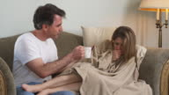 MS Man giving tea to sick woman lying on sofa, Phoenix, Arizona, USA