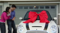 MS Man giving woman new sports car with red bow as surprise gift / Los Angeles, California, USA