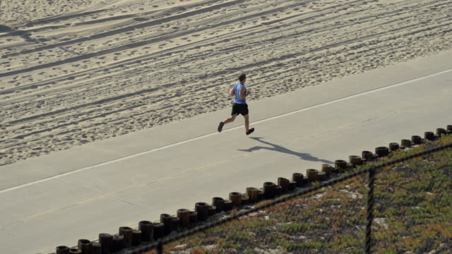 A man going for a run by the beach. - Slow Motion