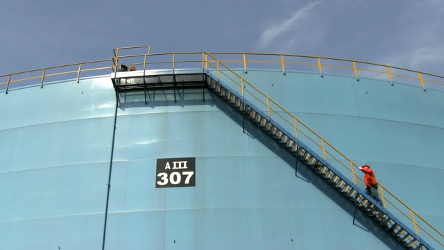MS Man going up stairs of oil refinery tank  / Hamburg, Germany