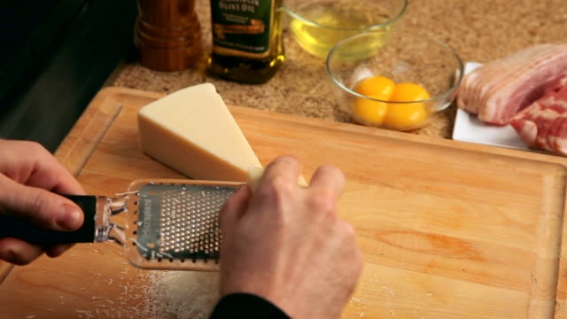 POV man grating parmesan cheese