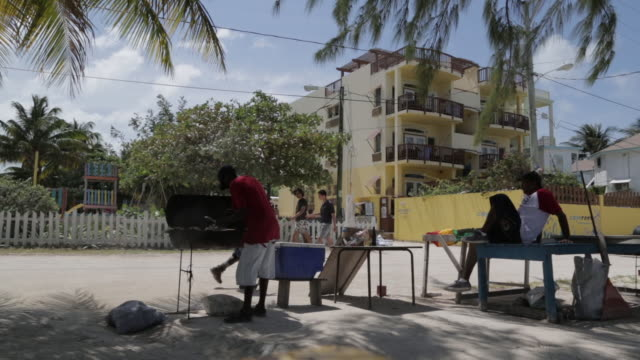 Man grills on the beach in Belize