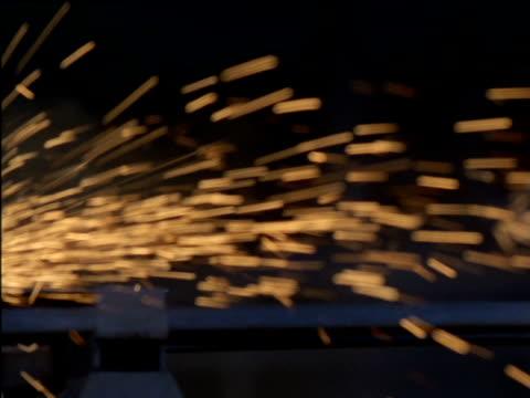 Man grinding metal in steel factory, South Africa