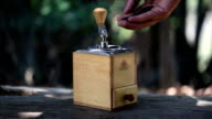 man grinds fresh roasted coffee beans with an antique style