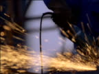 Man grinds steel creating sparks in factory, South Africa