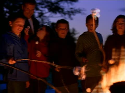 Man + group of children standing around campfire roasting marshmallows at dusk