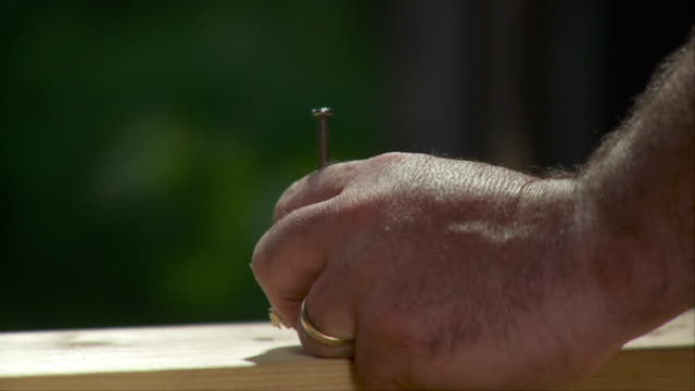 SLO MO CU Man hammering nail into plank, Stowe, Vermont, USA