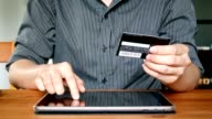 man hand holding credit card and using digital tablet computer touchscreen for online shopping or electronic banking at home