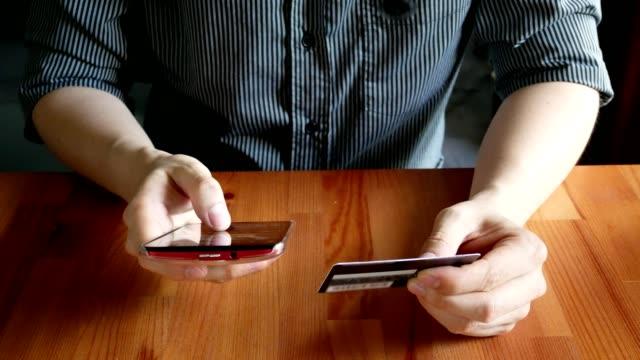Hand des Mannes hält Kreditkarte und Handy für Online-shopping