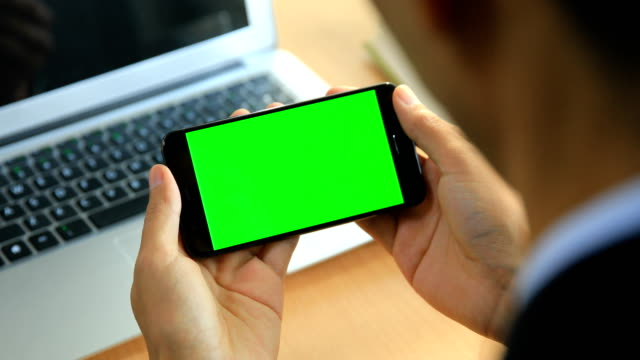 Man hand holding green screen mobile phone