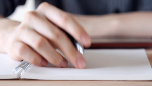 man hand tapping his finger, thinking what to write - writing education concept