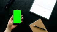 man hand using mobile phone with green screen on office table - top view