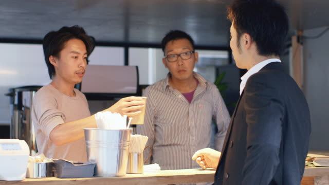 WS A man hands over a cup of coffee in a Tokyo cafe / Tokyo, Japan