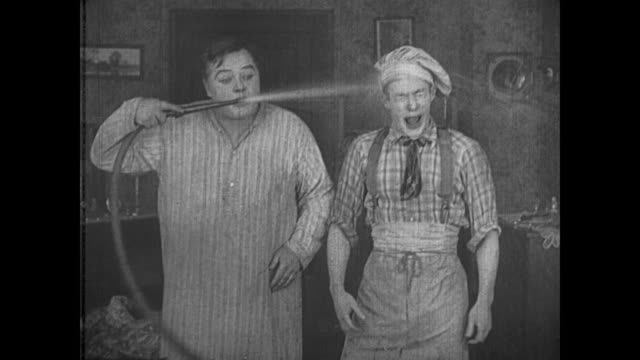 Fatty Arbuckle has trouble controlling a hose while trying to put out a fire and soaks everyone in the house
