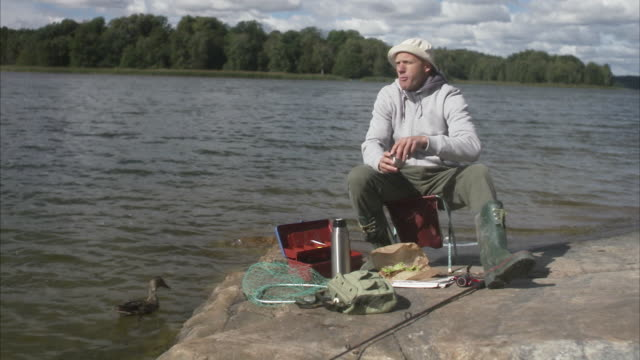 A man having a coffee break during a fishing tour Sweden.