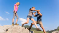 Man helping women to jump gap in mountain boulder