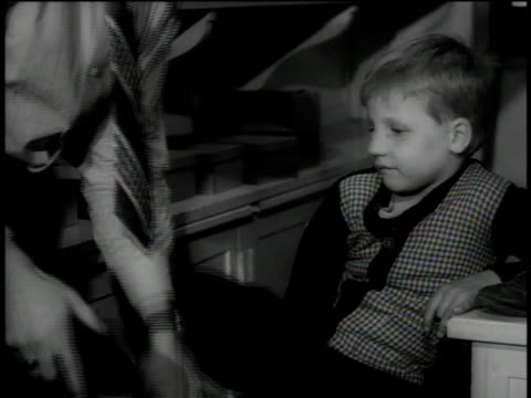 1946 MS Man helps a little boy tie his shoes