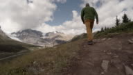 Man hikes alpine trail, snow capped mountains and cloudy
