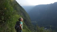 Man hikes to edge of mountain path, looks off