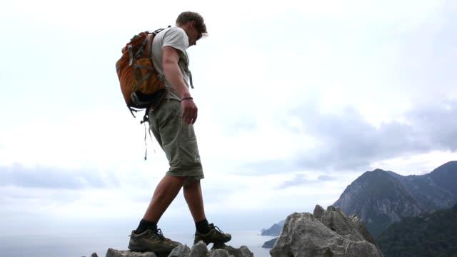 Man hikes to ridge crest above sea, mountains