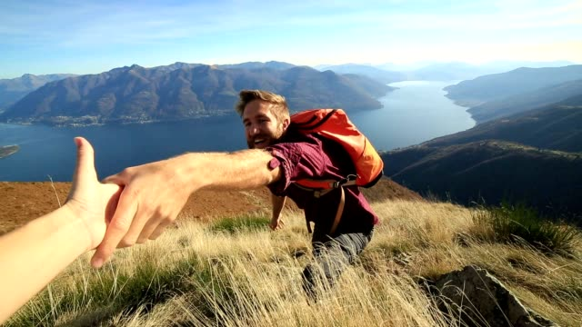 Man hiking on difficult terrain, hand reach out to assist