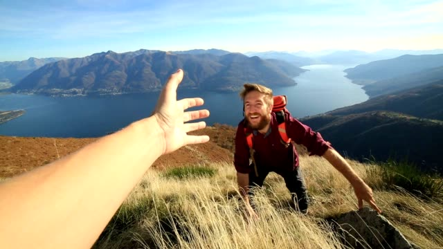 Man hiking uphill, hand reach out to help