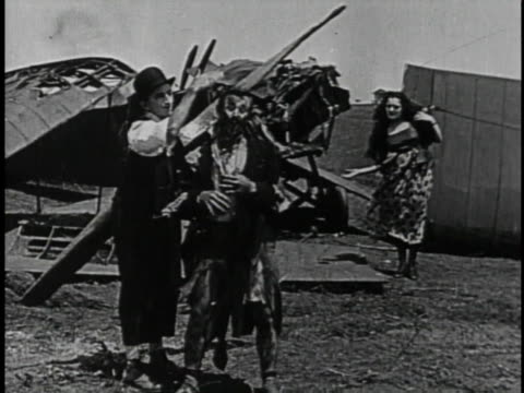 1920 WS Man hitting another man over the head with an airplane propeller while woman looks on