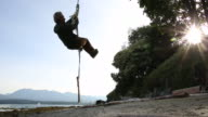 Man hoists himself up rope swing, from beach below