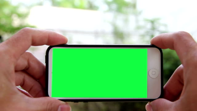 man hold smart phone by green screen condition