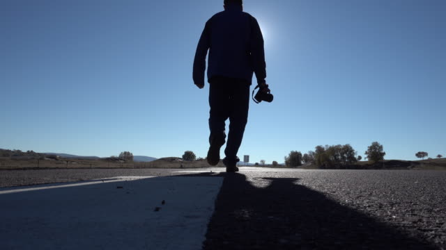 Man holding a camera and walking on the road