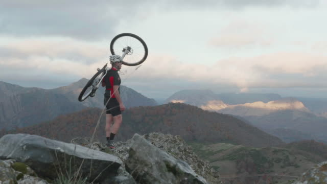 Man holding a mountain bike in the top of a mountain looking at the horizon