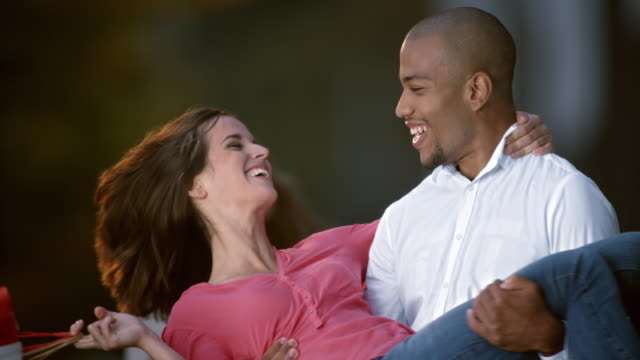 SLO MO man holding a woman in his arms, spinning and smiling